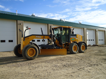 One of the 770G John Deere Graders that Jade Oilfield Maintenance currently has, parked in front of the Edson shop
